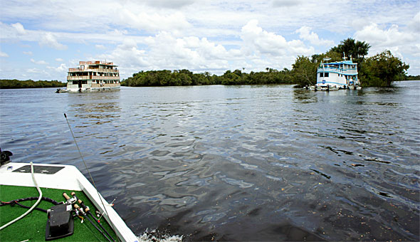 Amazon Otter houseboat and the guides boat on the Rio Negro