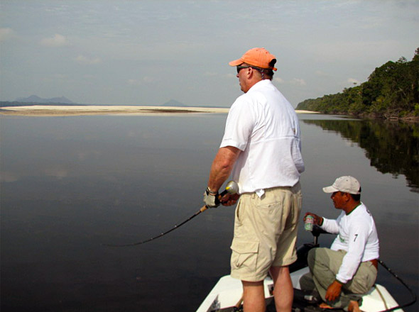 Nick Owings rips his woodchopper topwater nears sandbars far up the Rio Negro with low mountains and ancient volcanoes in the distance while expert river peacock bass guide G advises.